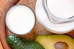 Avocado die op een witte achtergrond wordt ge?soleerd Met glas van melk en houten plaat Gezond voedsel Stock Foto