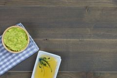 Avocado dip or guacamole with honey on wood table Royalty Free Stock Photo