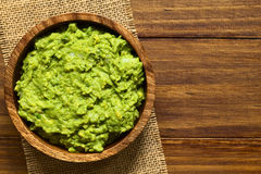 Avocado Dip or Guacamole. In wooden bowl, photographed overhead with natural light (Selective Focus, Focus on the avocado dip Stock Photo