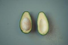 Avocado divisi in due su fondo di legno Fotografie Stock Libere da Diritti