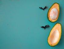 Avocado divisi in due su fondo di legno Immagini Stock