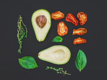 Avocado, dried tomatoes, green basil leaves and thyme on a black Stock Images