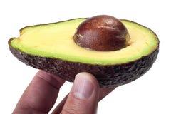 Avocado in een hand Royalty-vrije Stock Afbeeldingen
