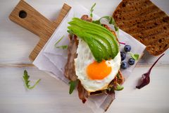 Avocado, egg and bacon sandwich. Fried egg and avocado on toast. Panini. Healthy tasty food for breakfast or brunch. Avocado, egg and bacon sandwich. Fried egg Stock Photos
