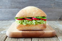 Avocado, egg salad sandwich on ciabatta bun over rustic wood Stock Photos