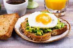 Avocado egg sandwich with whole grain bread. On wooden background. Copy space stock image