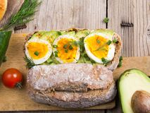 Avocado and egg sandwich on a wooden background. Royalty Free Stock Photos