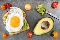 Avocado, egg toast with tomatoes on rustic baking tray. Open avocado, egg sandwich on whole grain bread with cherry tomatoes on rustic baking tray royalty free stock photos