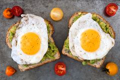 Avocado, egg toast with tomatoes on rustic baking tray Royalty Free Stock Image