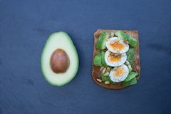 Avocado eggs on brown toast and dark background Stock Photo