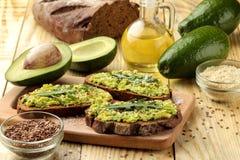 Avocado en arugulasandwiches en andere ingrediënten op een natuurlijke houten lijst Sandwich met avocadopuree royalty-vrije stock foto