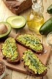 Avocado en arugulasandwiches en andere ingrediënten op een natuurlijke houten lijst Sandwich met avocadopuree stock foto