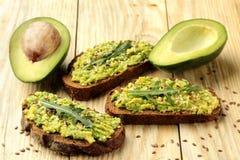 Avocado en arugulasandwiches en andere ingrediënten op een natuurlijke houten lijst Sandwich met avocadopuree stock foto's