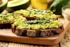 Avocado en arugulasandwichesclose-up op natuurlijke houten lijst Sandwich met avocadopuree stock foto's