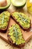 Avocado en arugulasandwichesclose-up op natuurlijke houten lijst Sandwich met avocadopuree royalty-vrije stock afbeelding