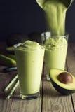 Avocado Erschütterung oder Smoothie, die in Gläser gegossen wird lizenzfreies stockbild