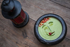 Avocado face. Avocado soup smile-shaped in a wooden table with red lamp royalty free stock image