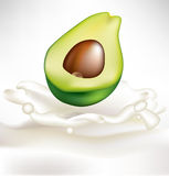 Avocado falling in milk splash Stock Photo