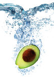 Avocado falls deeply under water. Fresh Avocado dropped into water with splash isolated on white stock photography