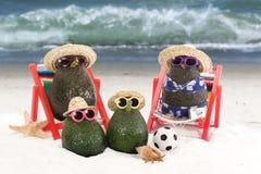 Avocado-Familie am Strand lizenzfreie stockfotos