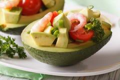 Avocado farcito con la macro dell'insalata del gamberetto su un piatto orizzontale immagini stock