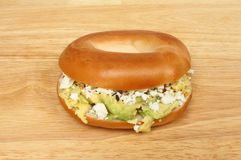Avocado and feta bagel. On a wooden chopping board stock image