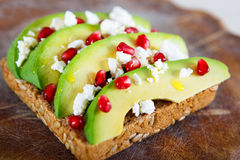 Avocado with Feta, pomegranate on sunflower seeds bread sandwich Stock Images