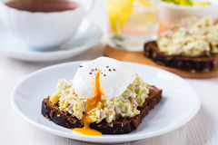 Avocado and feta smash on rye bread and poached  egg on top Stock Photos