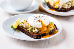 Avocado and feta smash on rye bread and poached  egg on top Royalty Free Stock Photo