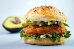 Avocado fish sandwich. Avocado fish burger with brioche bun , mayonnaise and lettuce , flax seeds on top Stock Photography