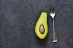 Avocado and fork on a black background with space for text. Diet. View from above. Avocado and fork on a black background with space for text. Diet food stock photos