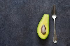 Avocado and fork on a black background with space for text. Diet. Avocado and fork on a black background with space for text. Diet food stock photos