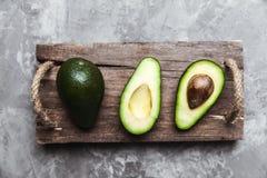 Avocado fresco affettato sopra la fine di legno d'annata del fondo su Di avocado verde maturo sul bordo di legno Immagini Stock Libere da Diritti