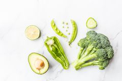 Avocado fresco, calce, broccoli, piselli, cetriolo, peperone verde Disposizione piana Concetto dell'alimento Verdure verdi che si fotografia stock libera da diritti