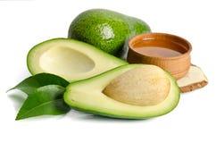 Avocado fresco con olio di avocado nella ciotola di legno Fotografia Stock