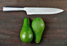 Avocado. Fresh avocado and iron knife  on wood table background. Tasty and health vegetable. Exotic fruit Royalty Free Stock Images