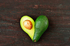 Avocado. Fresh avocado in the shape of a heart  on wood table background. Love symbol made of fruit. Exotic fruit Stock Photos