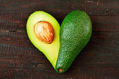 Avocado. Fresh avocado in the shape of a heart  on wood table background. Love symbol made of fruit. Exotic fruit Royalty Free Stock Images