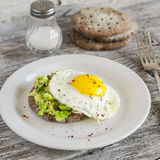Avocado and a fried egg sandwich on a white plate stock images