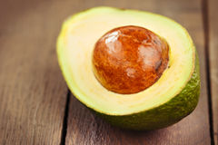 Avocado fruit on brown wooden old table Stock Photo