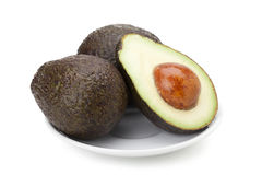Avocado fruit. In ceramic plate isolated on white background with clipping path and soft shadow Stock Photos