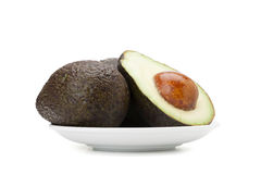 Avocado fruit. In ceramic plate isolated on white background with clipping path and soft shadow Royalty Free Stock Photo