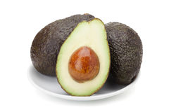 Avocado fruit. In ceramic plate isolated on white background with clipping path and soft shadow Stock Image
