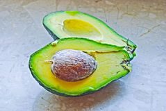 Avocado fruit. Cut into two halves with its pit Stock Photo