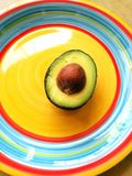 Avocado fruit half. A photograph showing a cut half pear of an avocado with seed intact and placed on a bright colorful plate with Mexican ring colors. Health royalty free stock images
