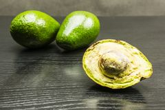 Avocado fruit - section. Avocado fruit - section Hass avocado Bilse avocado. Green fruits in the background Stock Photos