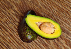Avocado fruit on a wood background. With focus on core Stock Photography