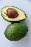 Avocado Ganzes und Hälfte mit Samen lizenzfreie stockbilder