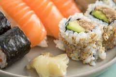 Avocado giapponese del tonno dentro - fuori California con Nigiri e Maki di color salmone sul piatto del preparato dei sushi fotografie stock libere da diritti