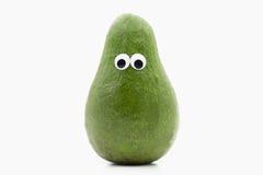 Avocado with googly eyes on white background Stock Image